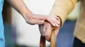 Close up of a hand on a cane and a caregiver's hand gently on top of the other hand
