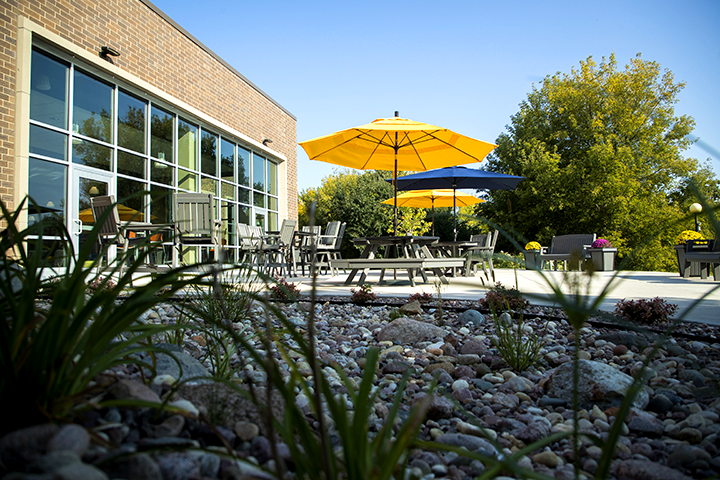 Outside view of New Richmond campus with patio tables