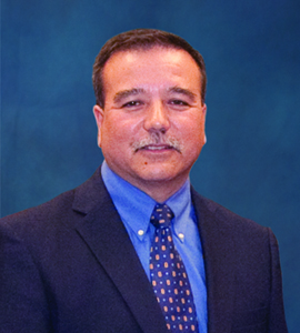 Image of board member Michael BeBeau wearing a black suit coat over a blue shirt with a tie.