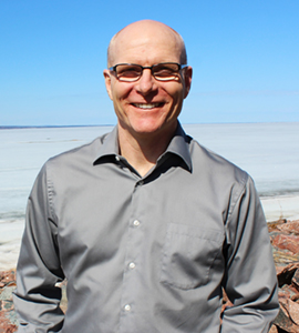 Image of distinguised alumni Paul Gordon standing in front of a lake and wearing a button-up shirt.