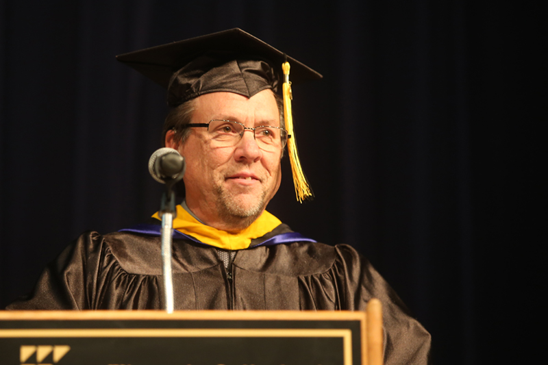Image of a past Distinguished Alumnus standing at a podium giving a speech for graduation, wearing a cap and gown.