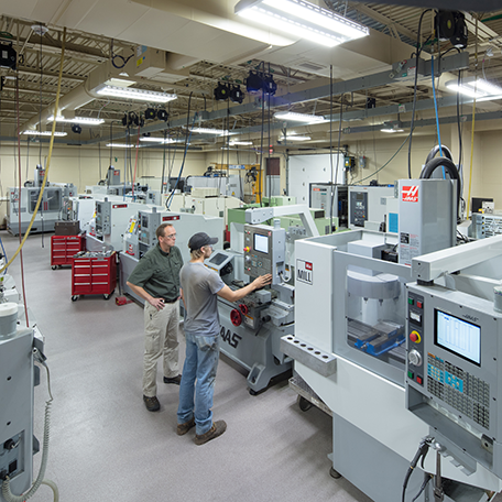 A view of the machine tool lab and a student using a cnc machine