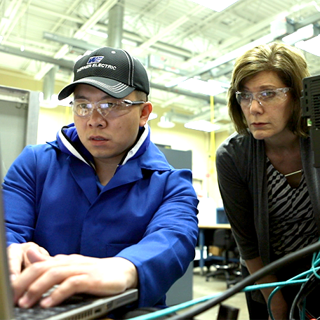 A student working on a computer with the instructor watching