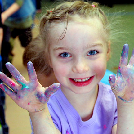 Young child smiling and holding up messy, sparkly hands