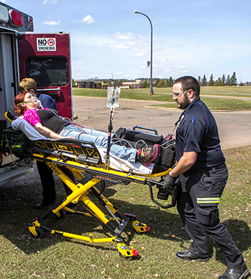 Two Advanced EMT students practicing loading a stretcher into an ambulance
