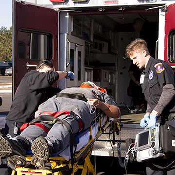 Paramedic students loading a stretcher onto an ambulance