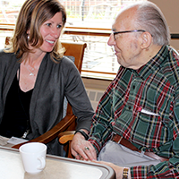 Director of an assisted living facility spending time with a resident