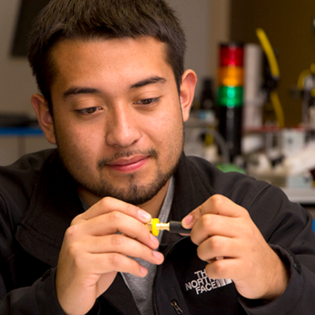 A student looking at a part used in mechatronics