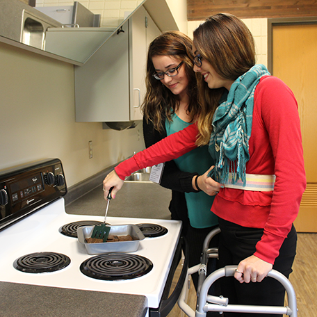 Students practicing how to assist someone in the kitchen