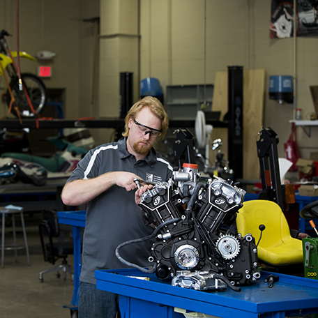 A student working on a motorcycle in the power sports lab