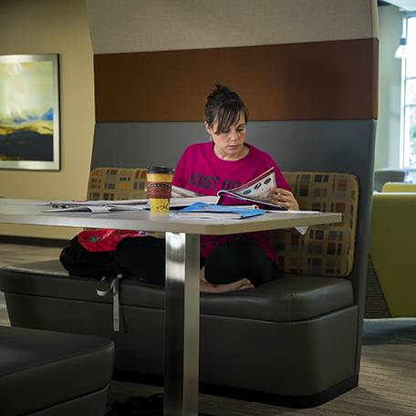 A student studying in a booth with a cup of coffee
