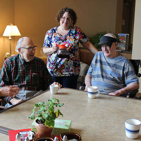 A healthcare service provider pouring coffee for residents of a community-based residential facility