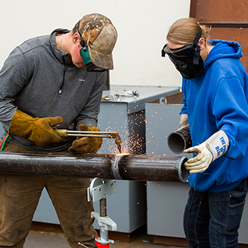 Two students welding a pipe