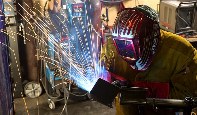 A welding student using the tools of the trade to weld
