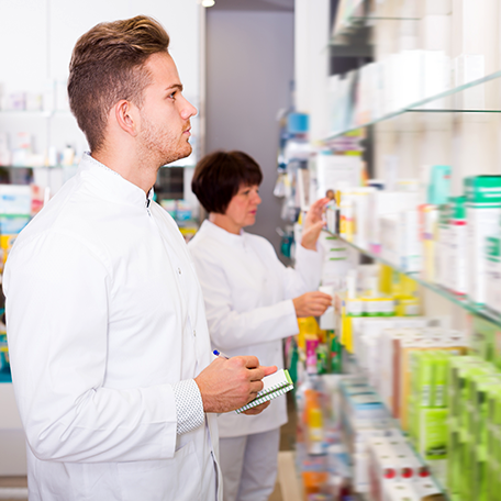 A pharmacy technician looking at a shelf of medications