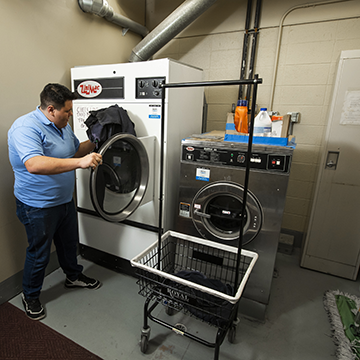 A hospitality foundation student doing laundry