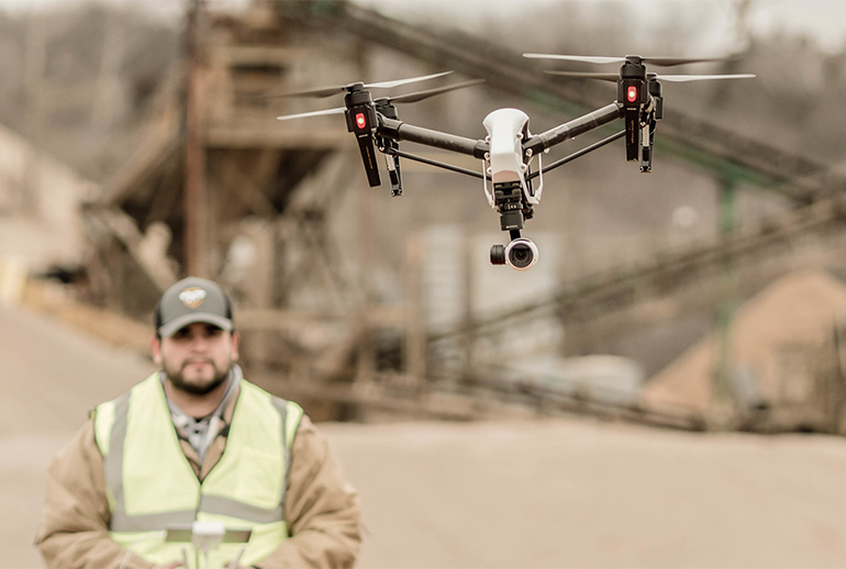 Image of a man in a safety vest controlling a drone with a construction scene in the background.