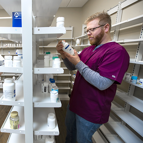 A pharmacy technician looking at a bottle of medicine