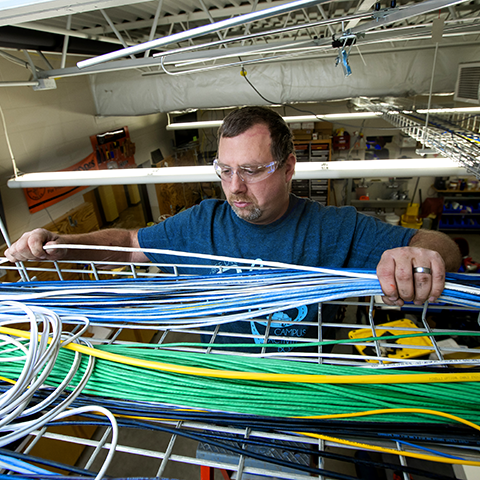 Broadband worker looking at cables