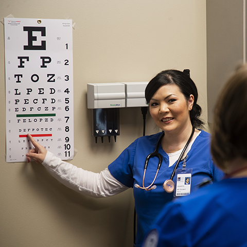 A medical assistant student performing an eye exam on a student patient