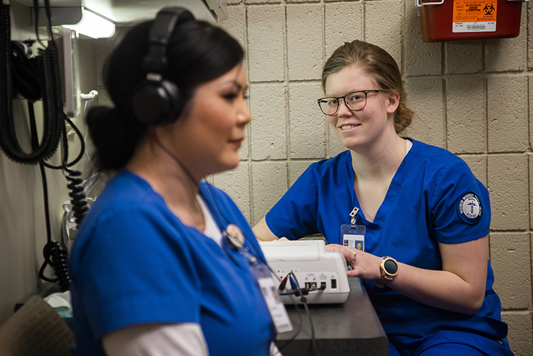 image of two female medical assistant students, one is testing the other's hearing