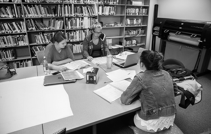Three girls sit around a large table in the library studying and talking.
