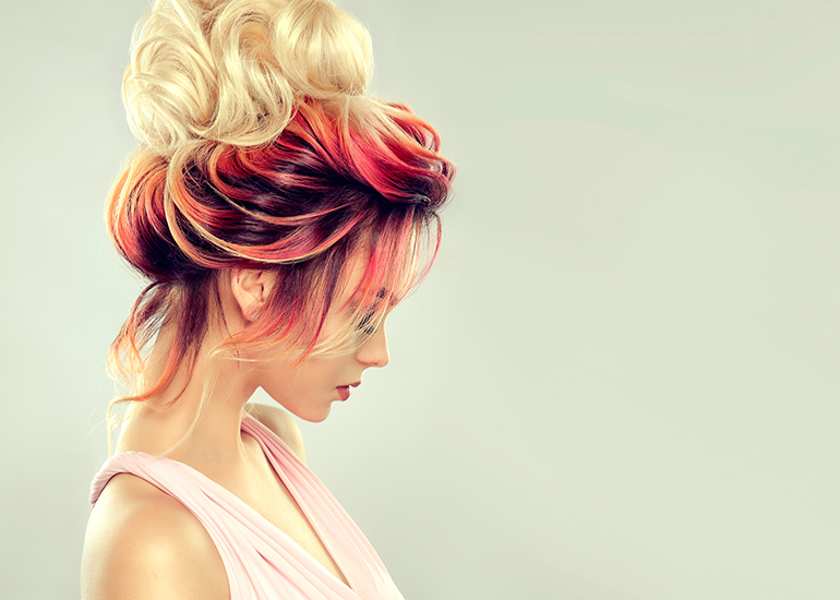 side profile of a woman with an updo containing pink and red lowlights