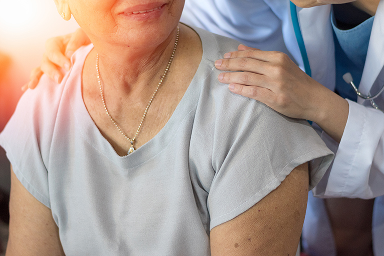 image of a female caregiver with her hand o the shoulder of an elderly woman