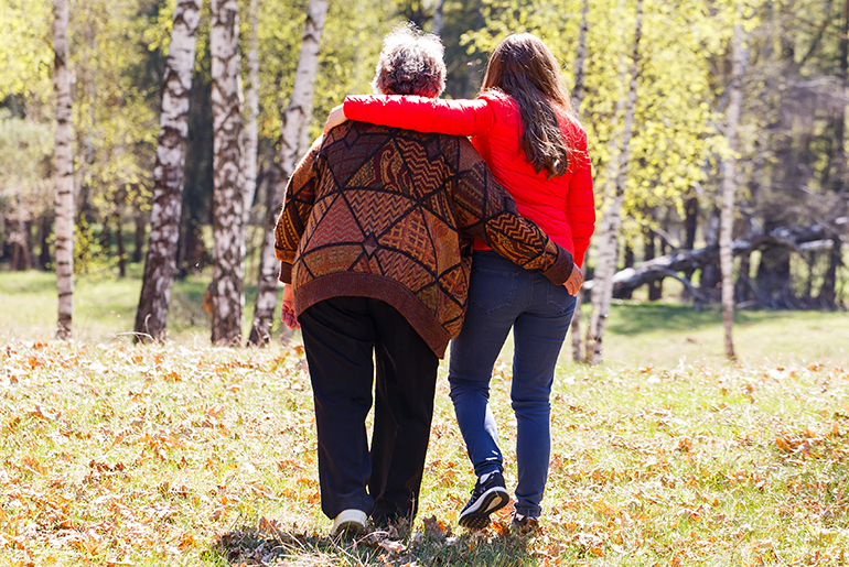 Back side image of a younger woman with her arm around an older woman walking through the woods.