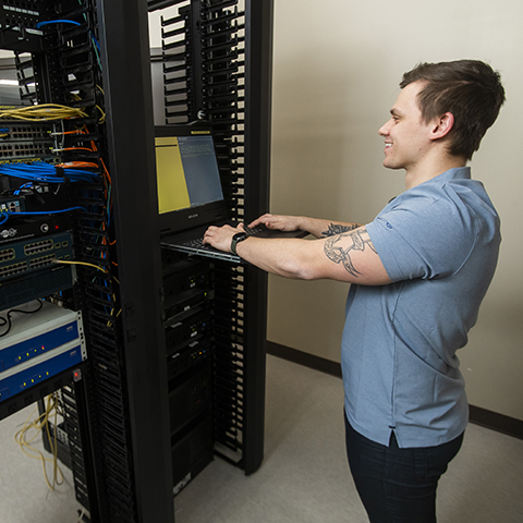 An IT - Cybersecurity Specialist student working hands-on with classroom technology