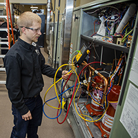 A student doing hands-on work in the HVAC industry