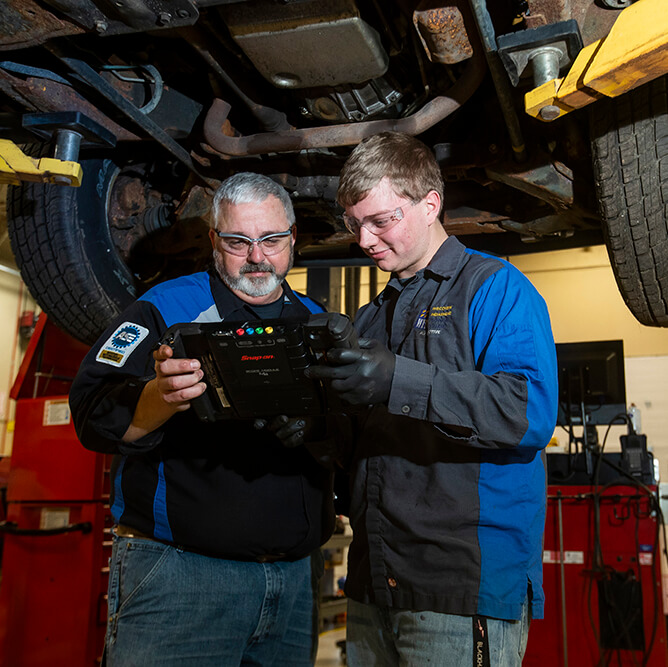 An automotive student and instructor looking at technology used in the automotive industry