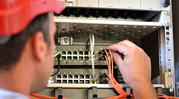 A broadband professional connecting fiber optic cable to the switch