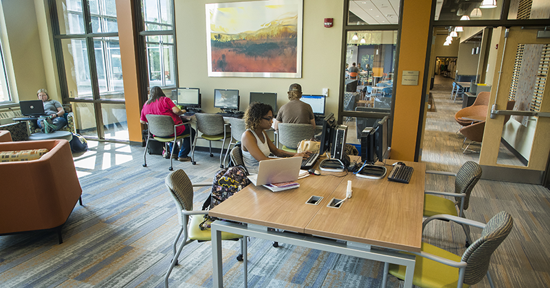 Students working on laptops and desktops and studying in the modern Learning Commons space in New Richmond