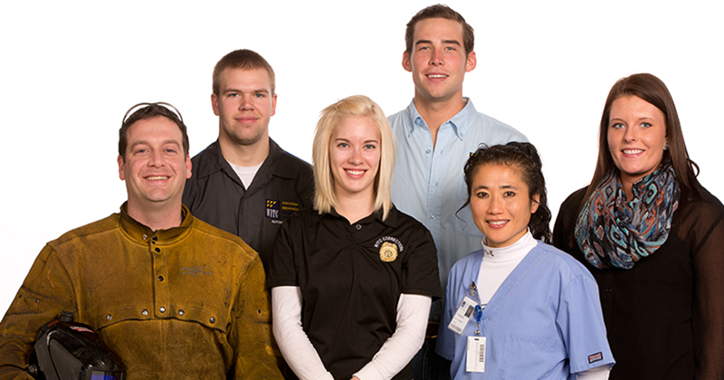 Students from various programs wearing their career outfits smile against a white background
