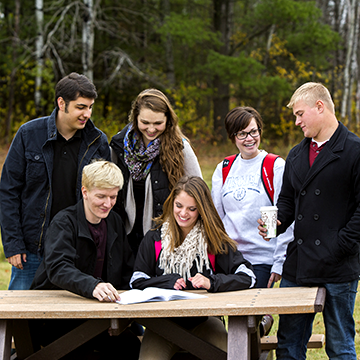 Group of students sitting at a picnic table and laughing