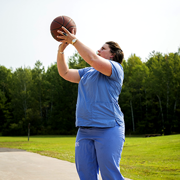 Student wearing a nursing uniform shooting a basket