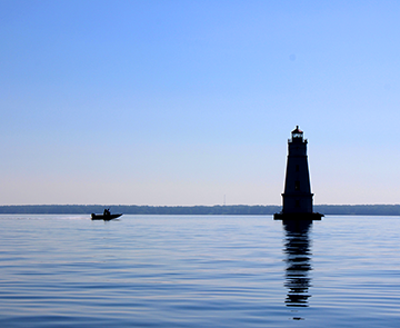 Silhouette of lighthouse and boat on Lake Superior