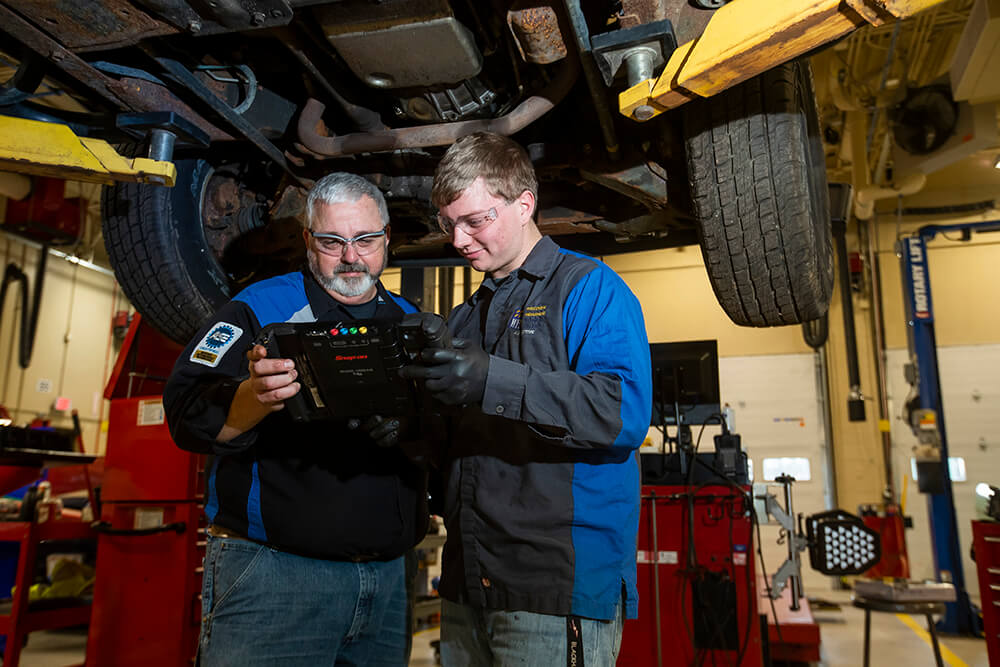 Automotive student with instructor examining the undercarriage of a truck