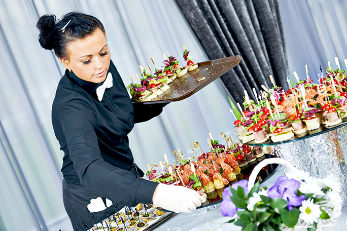 A caterer holding a tray of food