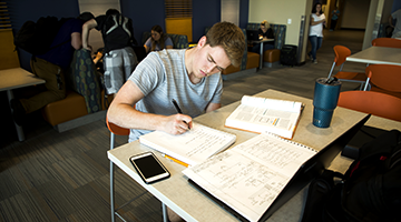 Student studying at a table with papers spread around
