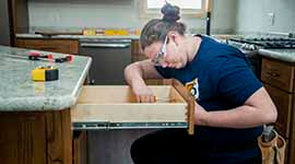 A student working on kitchen drawers in a house