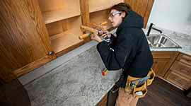 A student working on cabinetry in a house
