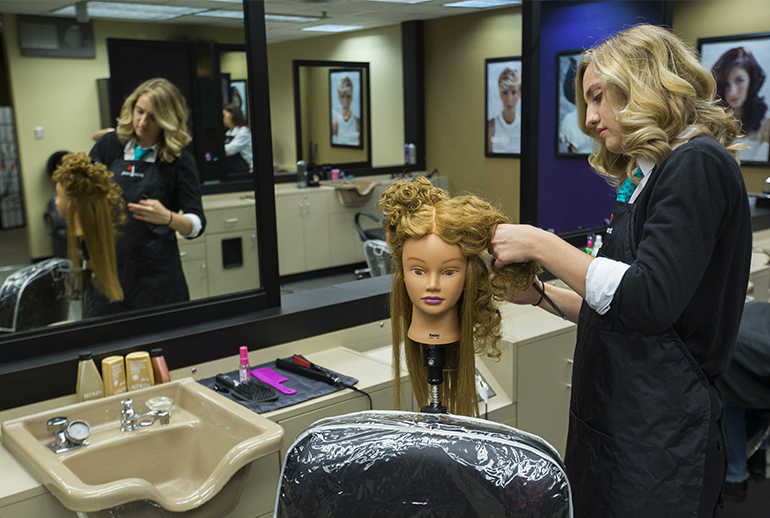 Image of a cosmetology student doing the hair of a mannequin in front of a mirror.