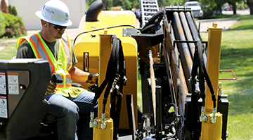 A utility construction student using a heavy machine