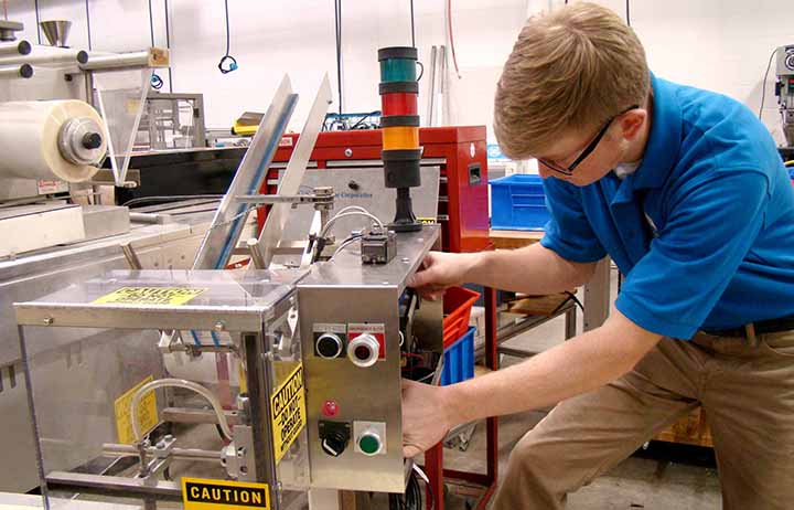 Student working with equipment in the automated packaging lab