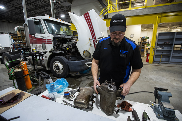 A diesel repair technician analyzing parts in a shop