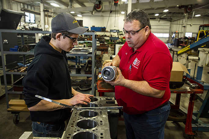 An instructor and student examining diesel equipment