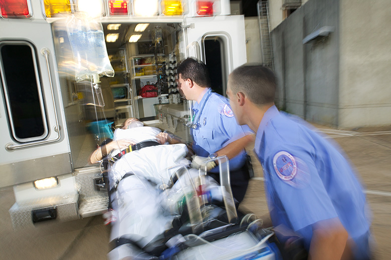 Paramedics load a patient into the back of an ambulance
