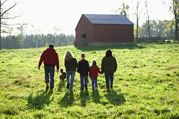 A family walking together by a barn